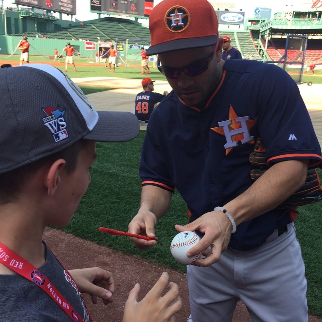 José Altuve signs a baseball for a fan at Fenway Park